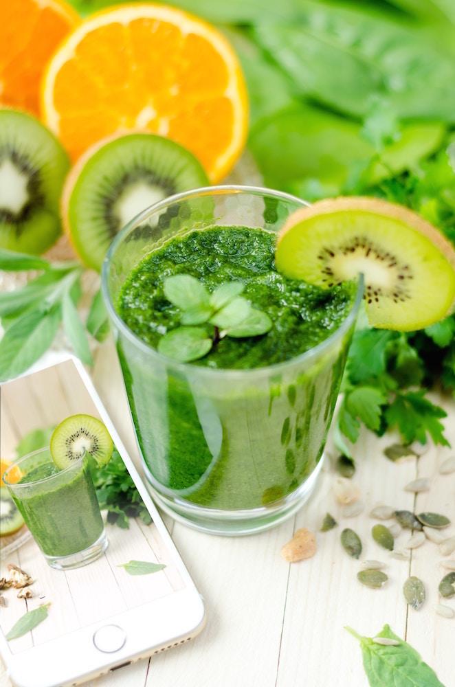 un jus vert et des tranches d'agrumes et de kiwi symboles de vitalité